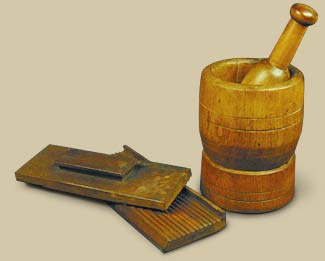 pill press (background) with mortar and pestle